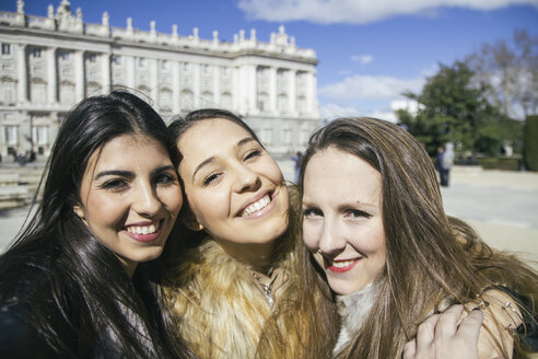 Spain, Madrid, three happy women taking a selfie in front of royal palace - ABZF000267