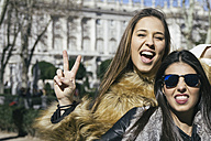 Spain, Madrid, two women posing in front of royal palace - ABZF000270