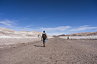 Chile, San Pedro de Atacama, Valley of the Moon, back view of hiker in the desert - MAUF000297
