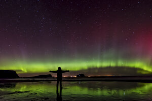 Scotland, East Lothian, silhouette of woman standing on Seacliff Beach watching Northern lights - SMAF000443