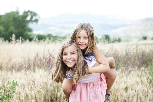 Spain, Girona, portrait of two happy sisters playing on a meadow - VABF000303