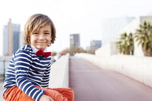 Spain, Barcelona, portrait of happy little boy wearing bow tie sitting on a wall - VABF000315