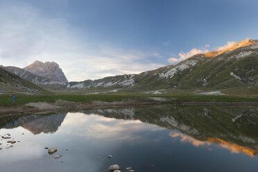 Italy, Abruzzo, Gran Sasso e Monti della Laga National Park, plateau Campo Imperatore, Corno Grande peak reflected in lake Petranzoni at sunset - LOMF000233