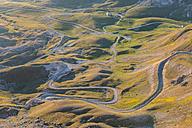 Italy, Abruzzo, Gran Sasso e Monti della Laga National Park, Snaky road on plateau Campo Imperatore at sunrise - LOMF000236