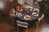 Boy at Christmas dinner table with Christmas crackers - MFF002828