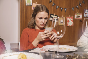 Woman playing with her smartphone after Christmas dinner - MFF002858
