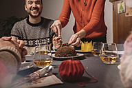 Christmas pudding is being cut on family table - MFF002864