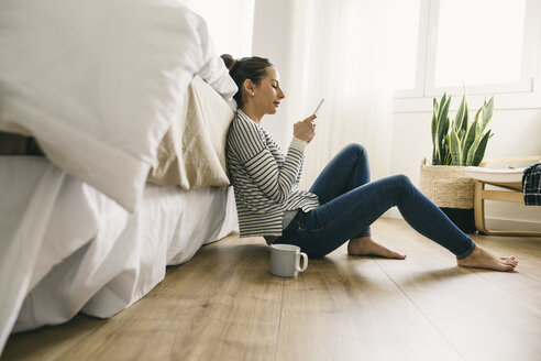 Relaxed woman sitting in bedroom looking at cell phone - EBSF001239