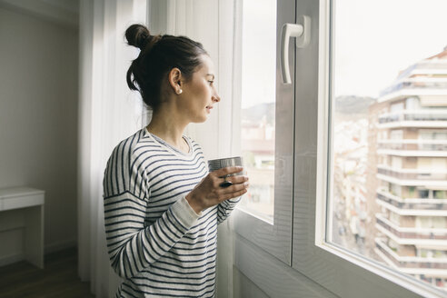 Woman holding cup of coffee looking out of window - EBSF001242