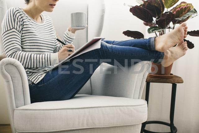 Woman sitting in armchair writing on notepad - EBSF001245 - Bonninstudio/Westend61