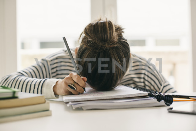 Woman writing on notepad resting her head on table - EBSF001251 - Bonninstudio/Westend61