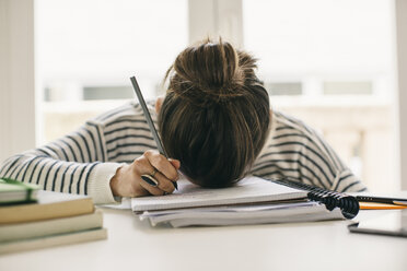 Woman writing on notepad resting her head on table - EBSF001251