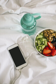 Drinking bottle, fruit bowl and smartphone with earphones on blanket - EBSF001263