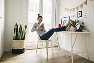 Woman at home laying feet on table looking at cell phone - EBSF001278