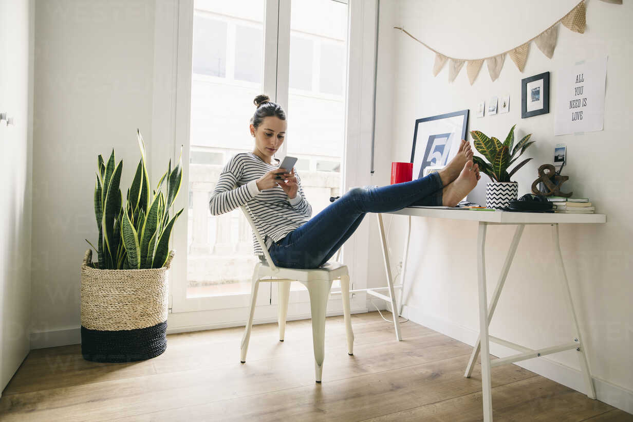 Woman at home laying feet on table looking at cell phone - EBSF001278 - Bonninstudio/Westend61
