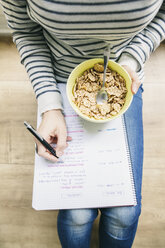 Woman sitting on floor with muesli bowl writing on notepad - EBSF001281