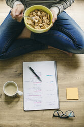 Woman sitting on floor with muesli bowl and notepad - EBSF001284