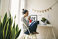 Woman at home sitting at table wearing headphones - EBSF001287