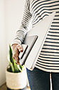Woman holding portable devices in different sizes - EBSF001290