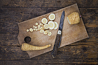 Sliced organic parsnips and pocket knife on chopping board - LVF004620