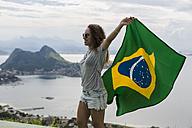 Brazil, woman with Brazilian flag on a viewpoint in Rio de Janeiro - MAUF000321