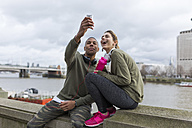 UK, London, two runners taking a selfie at riverwalk - BOYF000140