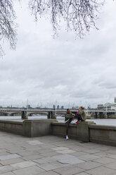 UK, London, two runners relaxing at riverwalk - BOYF000143