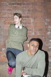 Stylish young couple at brick wall at night - BOYF000161