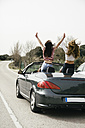 Women having fun in a convertible car on a country road - ABZF000279