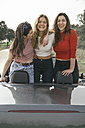 Three young woman laughing in a convertible car - ABZF000282