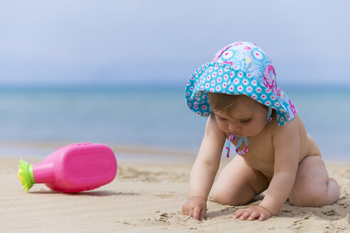 Naked little baby girl wearing summer hat playing on the beach - DSF000644
