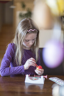 Girl painting Easter egg at home - SARF002628