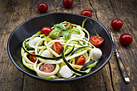 Bowl of zucchini spaghetti with mozzarella, cherry tomatoes and basil on wood - LVF004638