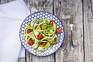 Bowl of zucchini spaghetti with mozzarella, cherry tomatoes and basil on wood - LVF004641