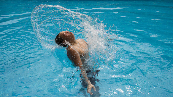 Boy splashing with water in a swimming pool - WGF000835
