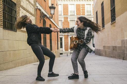 Spain, Madrid, two women dancing in a street - ABZF000283
