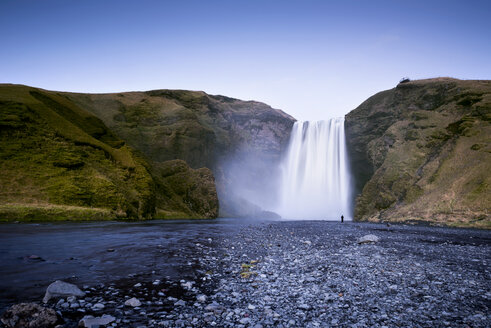 Iceland, person standing in front of Skogafoos waterfall - EPF000026