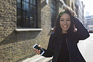 Portrait of happy young woman with cell phone on urban street - BOYF000180