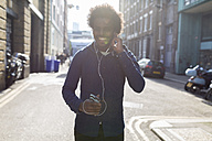 Young man listening to music from cell phone on urban street - BOYF000189