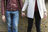Close-up of couple hand in hand in front of brick wall - BOYF000198