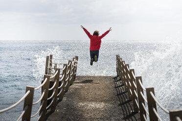 Portugal, Madeira, woman jumping on pier - MKFF000287