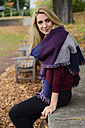 Portrait of relaxed young woman sitting on a wall in autumn wearing fashionable shawl - LFOF000186