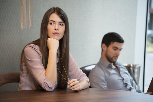 Thoughtful young woman with man in background - LFOF000198