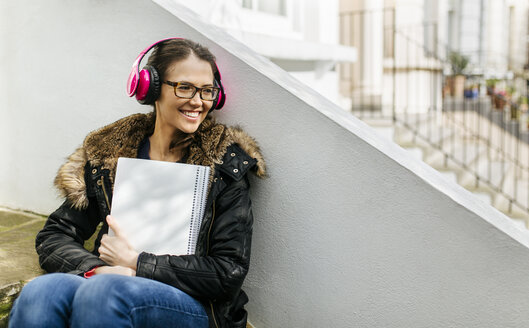 London, student girl with headphone and writing pad, language holiday - MGOF001522