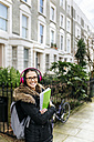 London, student girl with headphone and writing pad - MGOF001528