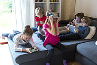 Five children on one couch using different digital devices - SARF002643