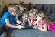 Five children on a couch using digital tablet together - SARF002646