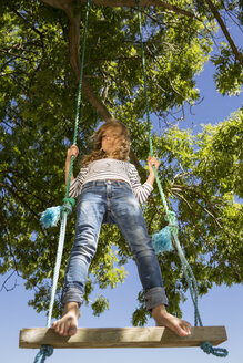 Girl standing on a swing - OJF000124