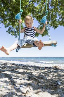 Portrait of blond boy sitting on a swing on the beach - OJF000127