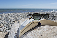 Sunglasses on opened book on pebble beach, close-up - OJF000130